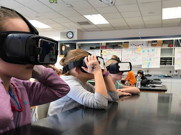 Students in science class with virtual reality goggles