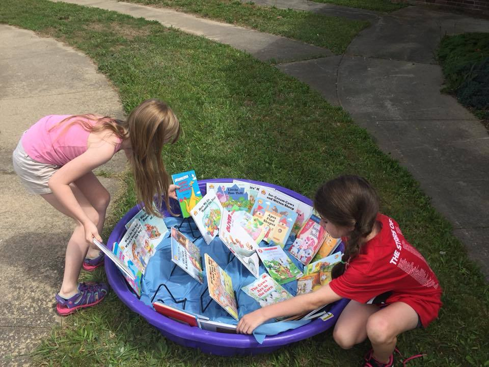 2 Girls looking at books in an outdoor wading pool